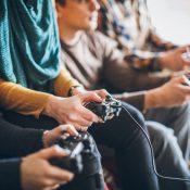 Groupe d'amis jouant à des jeux vidéo à la maison.